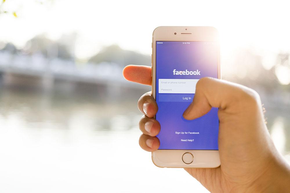 Person logging into Facebook social media