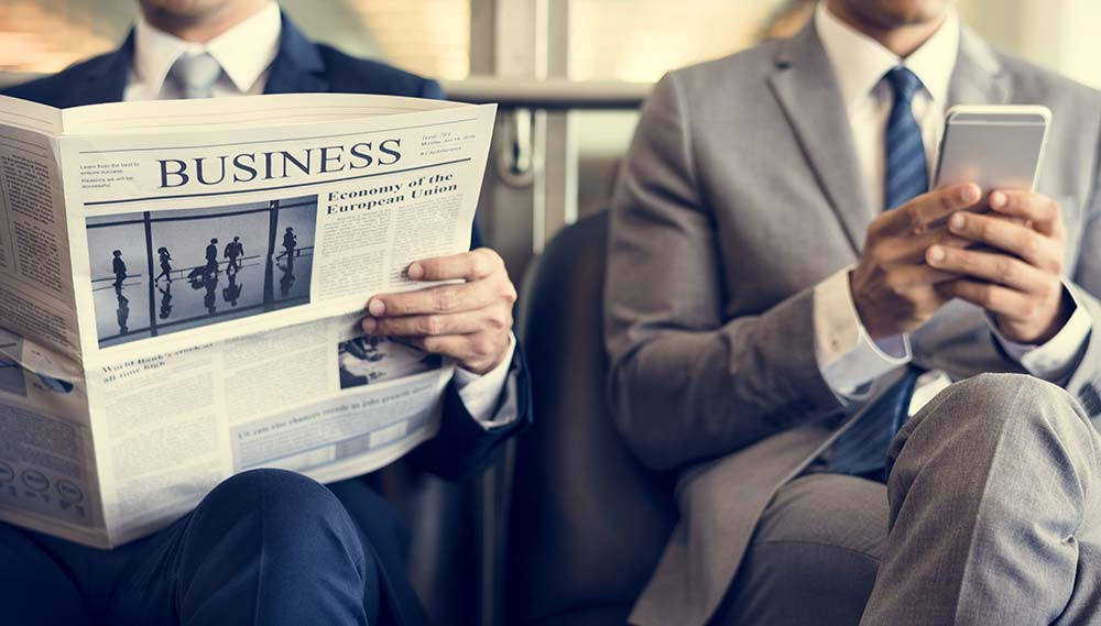 Business men reading news from a newspaper and smartphone